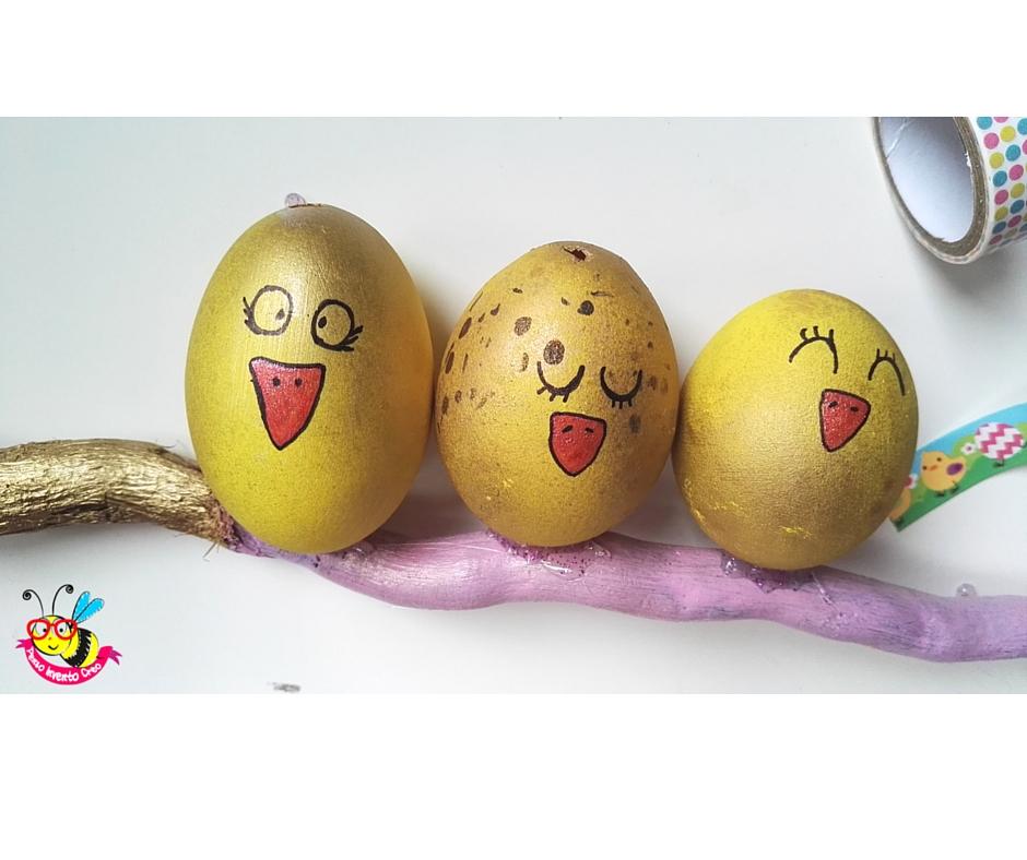 gusci di uova dipinti di giallo che sembrano pulcini attaccati ad un ramo, visti da vicino, con becchi ed occhi disegnati