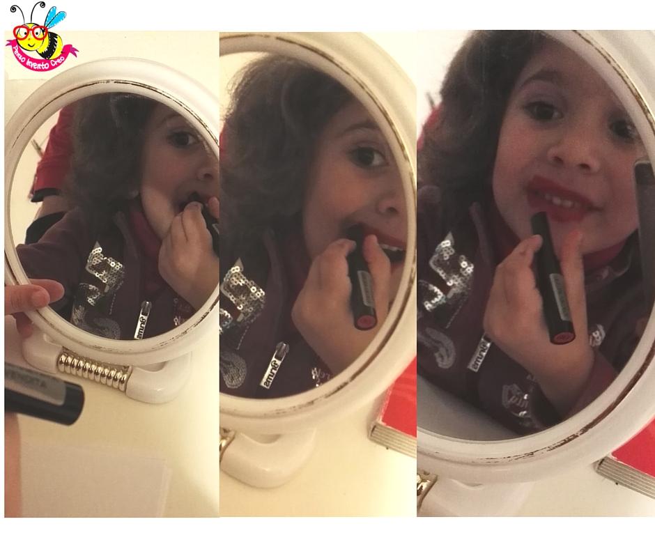 foto di bambina che si mette il rossetto: scatola che contiene dei baci stampati col rossetto su un foglio