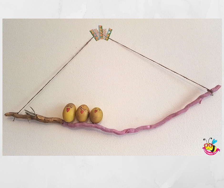 gusci di uova dipinti di giallo che sembrano pulcini attaccati ad un ramo, visti da lontano, sul ramo