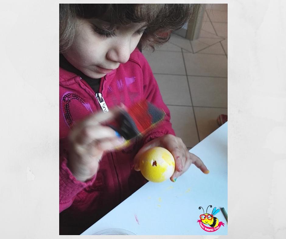 bambina che colora i gusci delle uova di giallo con una spugnetta